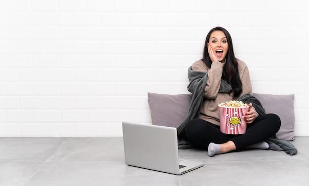 Jeune fille colombienne tenant un bol de pop-corn et montrant un film dans un ordinateur portable avec une expression faciale surprise et choquée