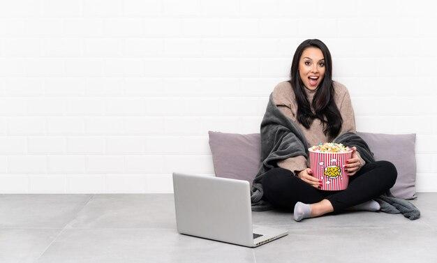 Jeune fille colombienne tenant un bol de pop-corn et montrant un film dans un ordinateur portable avec une expression faciale surprise
