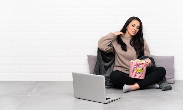 Jeune fille colombienne tenant un bol de pop-corn et montrant un film dans un ordinateur portable avec une expression fatiguée et malade