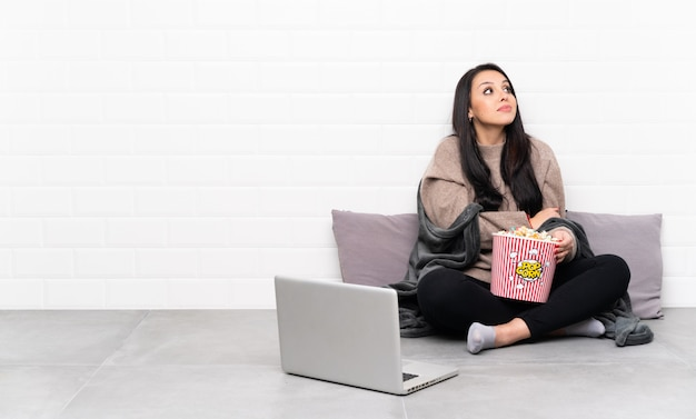 Jeune fille colombienne tenant un bol de pop-corn et montrant un film dans un ordinateur portable faisant des doutes en levant les épaules