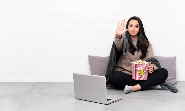 Jeune fille colombienne tenant un bol de pop-corn et montrant un film dans un ordinateur portable faisant un geste d'arrêt et déçu