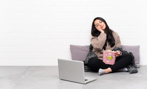 Jeune fille colombienne tenant un bol de pop-corn et montrant un film dans un ordinateur portable faisant un geste de sommeil dans une expression adorable