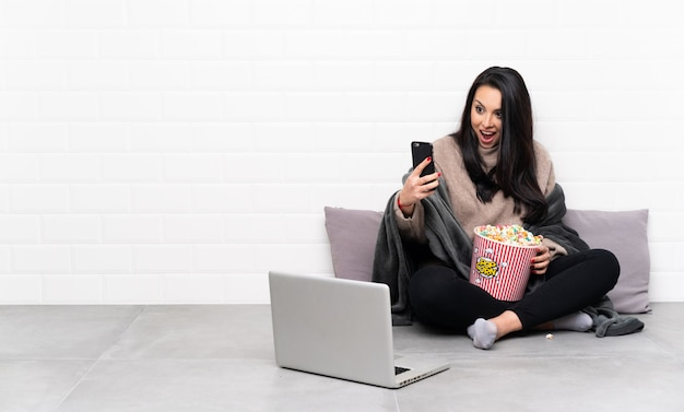 Jeune fille colombienne tenant un bol de pop-corn et montrant un film dans un ordinateur portable faisant un selfie