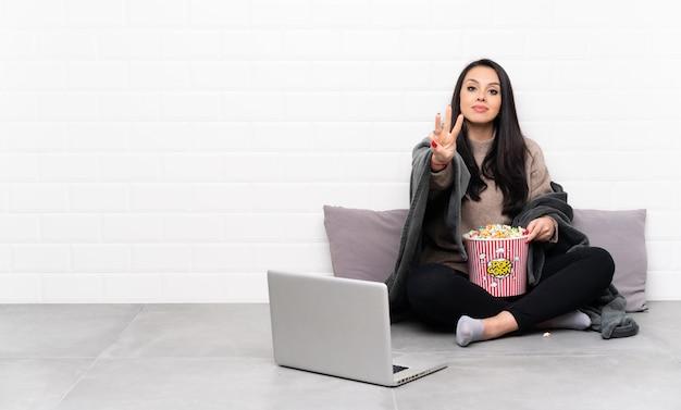 Jeune fille colombienne tenant un bol de pop-corn et montrant un film dans un ordinateur portable heureux et en comptant trois avec les doigts