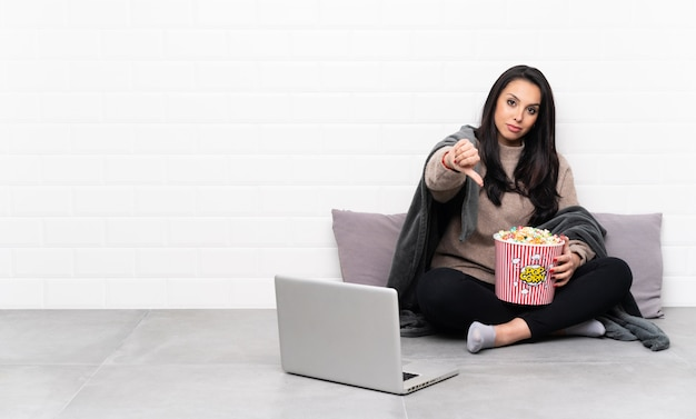 Jeune fille colombienne tenant un bol de pop-corn et montrant un film dans un ordinateur portable montrant le pouce vers le bas avec une expression négative