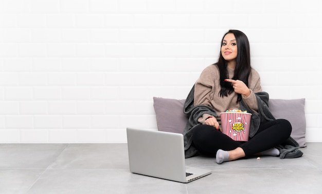 Jeune fille colombienne tenant un bol de pop-corn et montrant un film dans un ordinateur portable pointant vers l'arrière