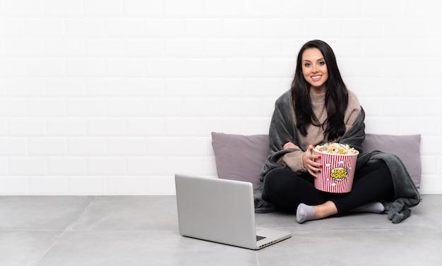 Jeune fille colombienne tenant un bol de pop-corn et montrant un film dans un ordinateur portable posant avec les bras à la hanche et souriant