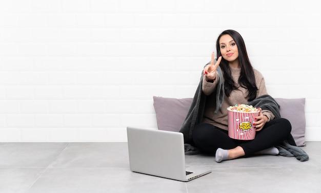 Jeune fille colombienne tenant un bol de pop-corn et montrant un film dans un ordinateur portable souriant et montrant le signe de la victoire