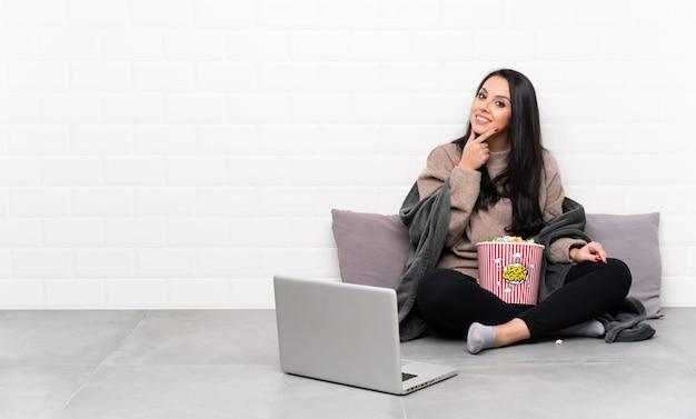Jeune fille colombienne tenant un bol de pop-corn et montrant un film dans un ordinateur portable souriant