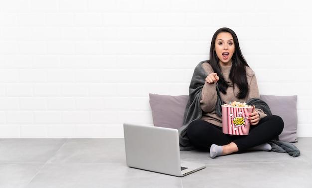 Jeune fille colombienne tenant un bol de pop-corn et montrant un film dans un ordinateur portable surpris et pointant vers l'avant