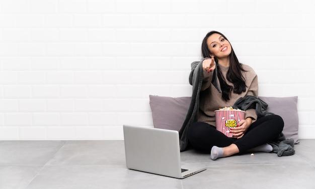 Jeune fille colombienne tenant un bol de pop-corn et montrant un film dans un ordinateur portable vous montre du doigt avec une expression confiante