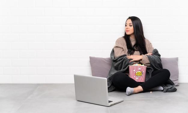 Jeune fille colombienne tenant un bol de pop-corn et montrant un film dans un portrait d'ordinateur portable