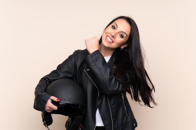 Jeune fille colombienne tenant un casque de moto sur un mur isolé célébrant une victoire