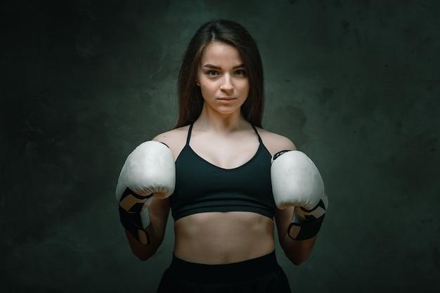 Jeune fille de combattant en colère avec des gants blancs pratique de combat