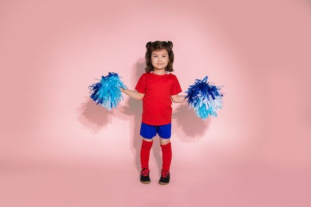 Jeune fille comme pom-pom girl sautant, enfant avec pompons bleus