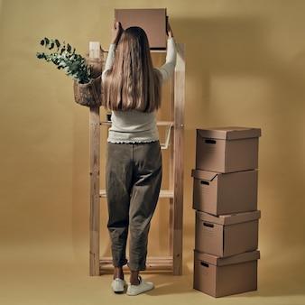 La jeune fille compose des boîtes en papier sur un support en bois. stockage et emballage écologiques.