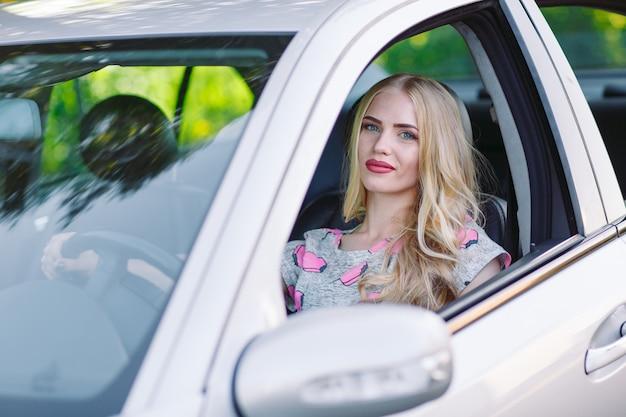 Une jeune fille conduit une voiture.