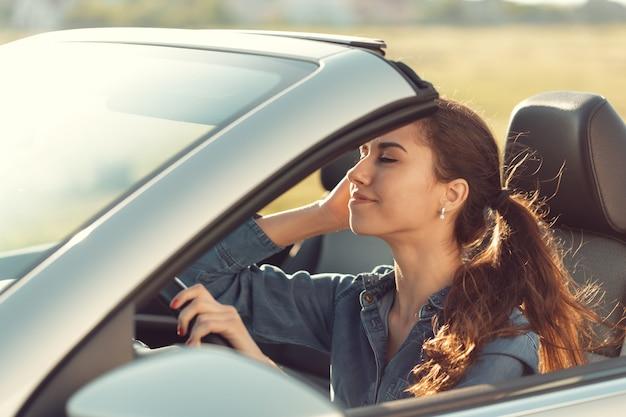 Jeune fille conduite voiture cabrio, à la lumière du coucher du soleil
