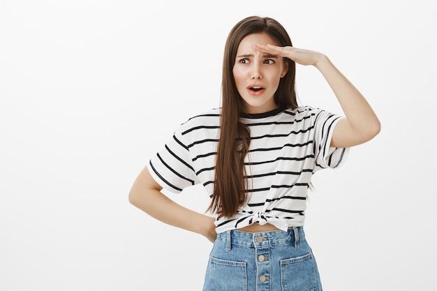 Jeune fille confuse et inquiète à la recherche de quelqu'un, tenant la main sur le front en regardant à distance