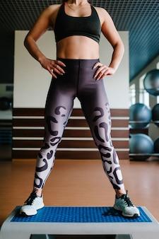 Jeune fille de corps de remise en forme en vêtements de sport et chaussures, jambes debout sur la plate-forme step.