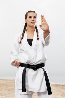 Jeune fille en costume d'arts martiaux en plein air