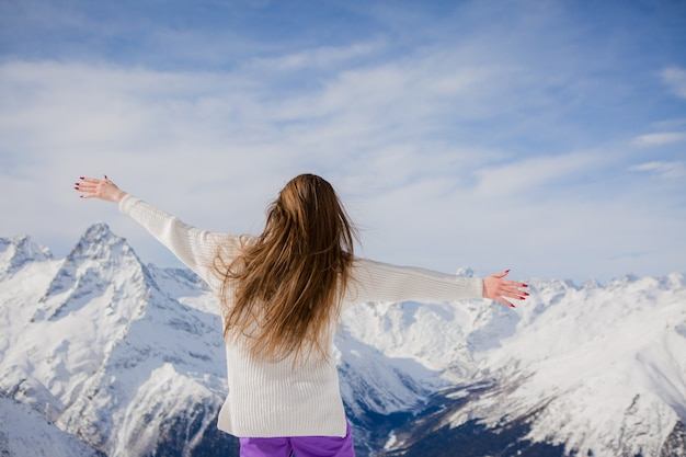 Jeune fille en costume d'hiver en regardant les montagnes