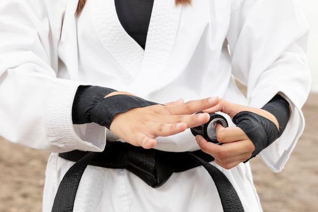 Jeune fille en costume de karaté et ceinture