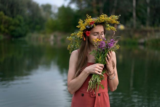 Jeune fille avec une couronne sur la tête tient un bouquet de fleurs sauvages sur la rivière. vacances ivan kupala.
