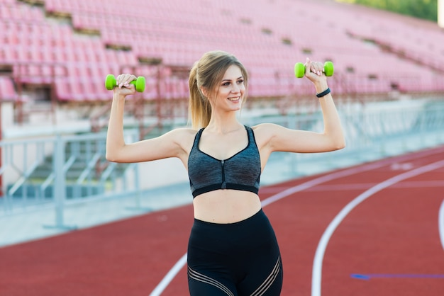 Jeune fille court avec des haltères dans les mains sur le stade. concept sportif et sain.