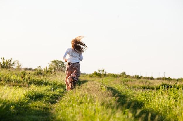 La jeune fille a couru à travers le champ. le concept de légèreté et sérénité, harmonie avec la nature