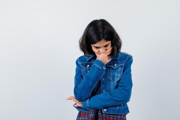 Jeune fille couvrant la bouche avec la main, pensant à quelque chose en chemise à carreaux et veste en jean et l'air songeur