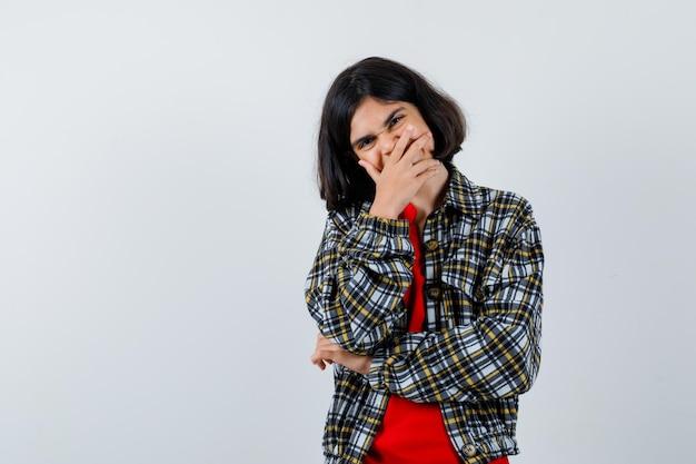 Jeune fille couvrant la bouche avec la main, riant en chemise à carreaux et t-shirt rouge et l'air heureux, vue de face.
