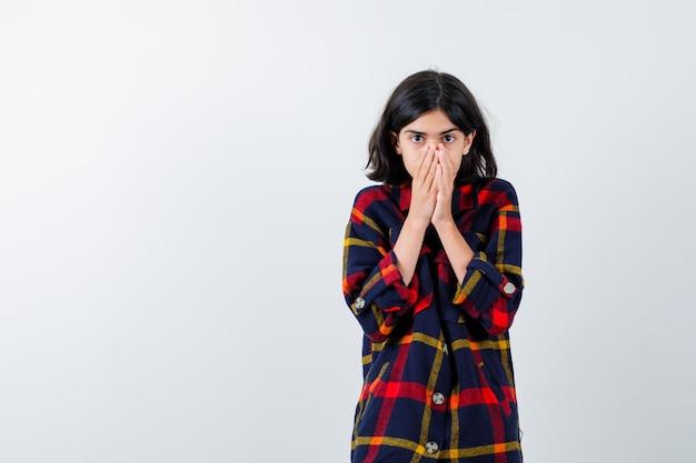 Jeune fille couvrant la bouche avec les mains en chemise à carreaux et l'air anxieux. vue de face.