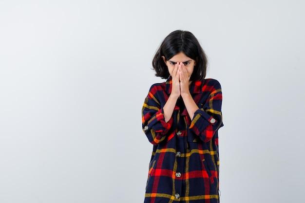 Jeune fille couvrant la bouche et le nez avec les mains en chemise à carreaux et l'air excité. vue de face.