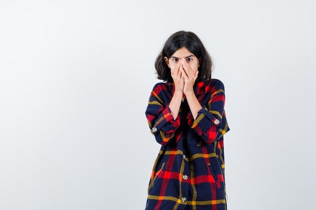 Jeune fille couvrant la bouche et le nez avec les mains en chemise à carreaux et l'air surpris. vue de face.