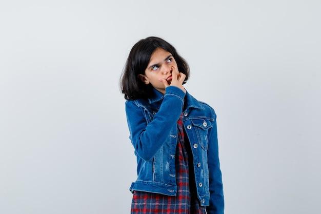 Jeune fille couvrant la main avec la bouche, regardant loin en chemise à carreaux et veste en jean et l'air pensif. vue de face.