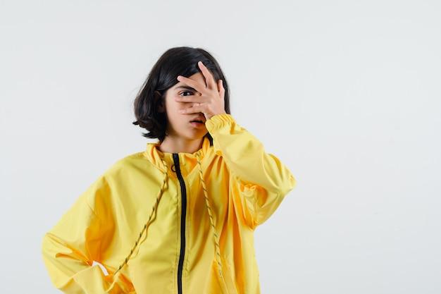 Jeune fille couvrant une partie du visage avec la main et regardant à travers les doigts en blouson aviateur jaune et à la grave