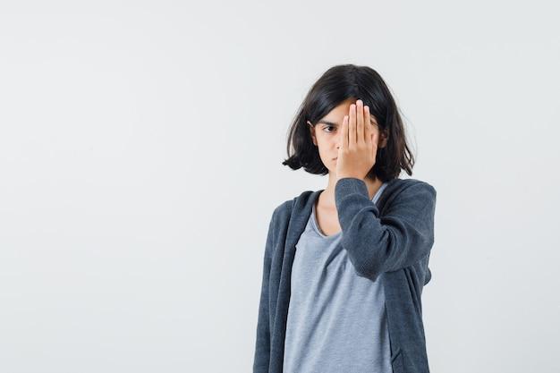 Jeune fille couvrant une partie du visage avec la main en t-shirt gris clair et sweat à capuche zippé gris foncé et à la jolie.