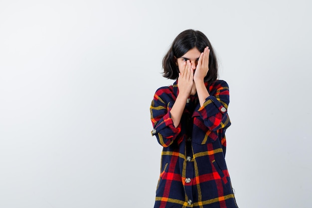 Jeune fille couvrant une partie du visage avec les mains en chemise à carreaux et l'air mignon, vue de face.