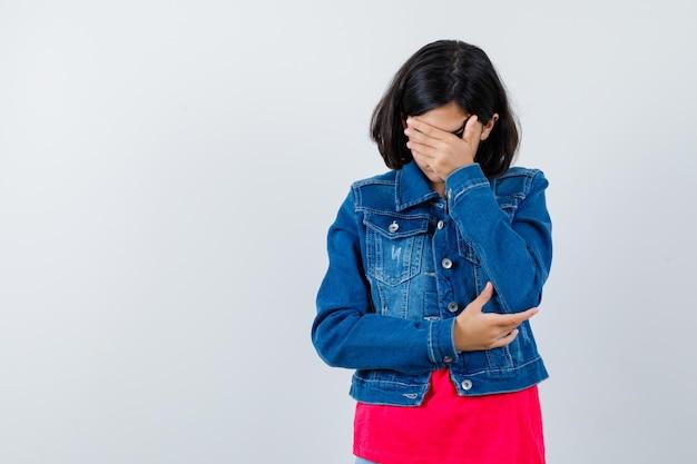Jeune fille couvrant le visage avec la main en t-shirt rouge et veste en jean et l'air harcelé. vue de face.