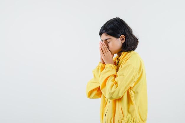 Jeune fille couvrant les yeux d'une main en bomber jaune et à la recherche de sérieux.