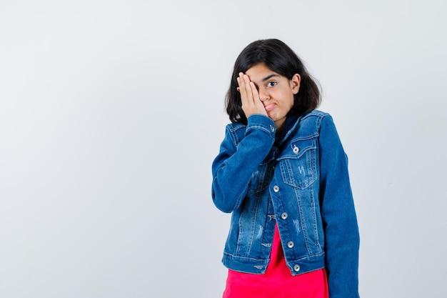 Jeune fille couvrant les yeux avec la main en t-shirt rouge et veste en jean et l'air heureux, vue de face.