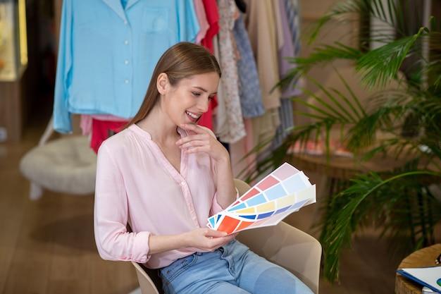 Jeune fille de créateur à succès avec des échelles de couleur à la main, assise sur une chaise devant le portant