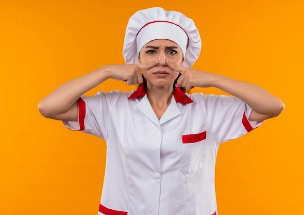 Jeune fille de cuisinier caucasien agacé en uniforme de chef ferme le nez avec les doigts isolés sur fond orange avec espace de copie