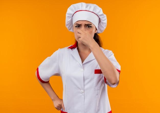 Jeune fille de cuisinier caucasien agacé en uniforme de chef ferme le nez avec la main isolé sur fond orange avec copie espace