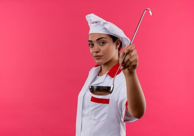 Jeune fille de cuisinier caucasien confiant en uniforme de chef se tient sur le côté et tient la louche isolé sur un mur rose avec espace de copie