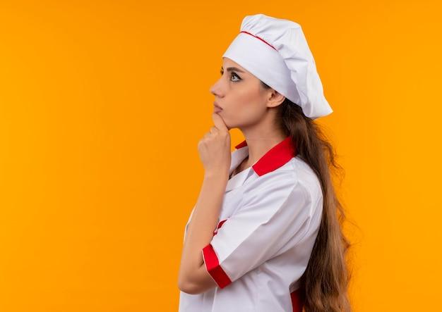 Jeune fille de cuisinier caucasien réfléchie en uniforme de chef se dresse sur le côté et ptuts main sur le menton isolé sur mur orange avec espace de copie
