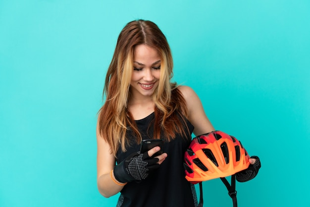 Jeune fille cycliste sur fond bleu isolé envoyant un message avec le mobile