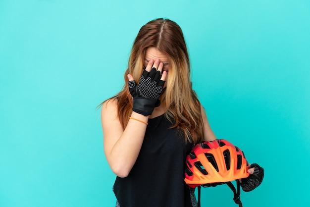 Jeune fille cycliste sur fond bleu isolé avec une expression fatiguée et malade