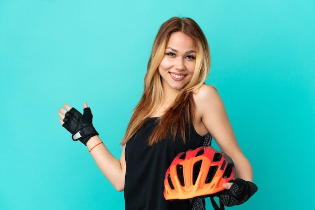 Jeune fille cycliste sur fond bleu isolé tendant les mains sur le côté pour inviter à venir